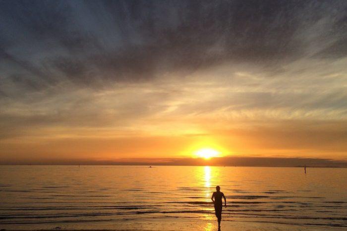 Bosco Soler corre mientras se pone el sol en una playa de Melbourne, Australia