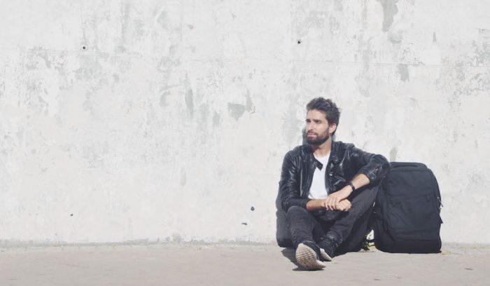 Bosco Soler sentado con una mochila en el suelo sobre una pared blanca