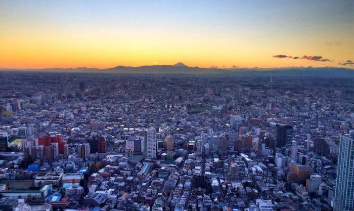 El sol poniéndose sobre la metrópolis de Tokio, con el monte Fuji de fondo.